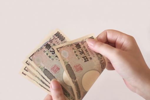 紙幣を数える女性の手の写真