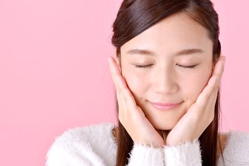 人物 女性 日本人 若者 若い 20代 美人 かわいい ロングヘア カジュアル ラフ 私服 セーター ニット 屋内 スタジオ撮影 背景 ピンク ピンクバック ポーズ おすすめ 頬 手を当てる 目を閉じる 微笑み 期待 顔 正面 アップ mdjf007