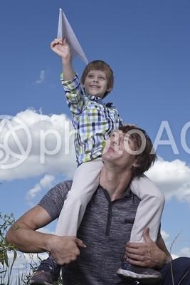 紙飛行機を飛ばす外国人の父子4の写真