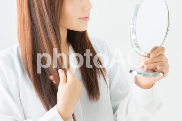 鏡で髪をチェックする女性の写真